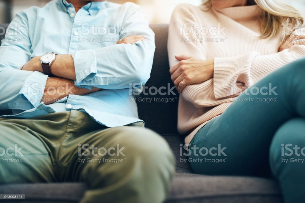 Every relationship has it's ups and downs Cropped shot of an unrecognizable mature couple sitting on the sofa with their arms folded after an argument Adult Stock Photo