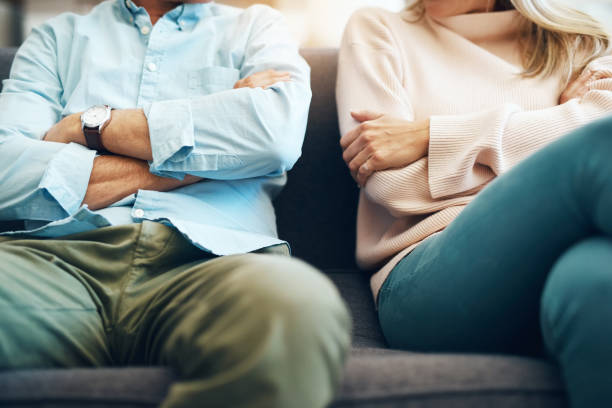 Every relationship has it's ups and downs Cropped shot of an unrecognizable mature couple sitting on the sofa with their arms folded after an argument agitation stock pictures, royalty-free photos & images