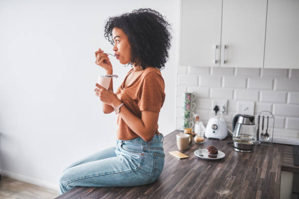 Every spoonful tastes like more Shot of a young woman having a tub of yoghurt in the kitchen at home probiotic stock pictures, royalty-free photos & images