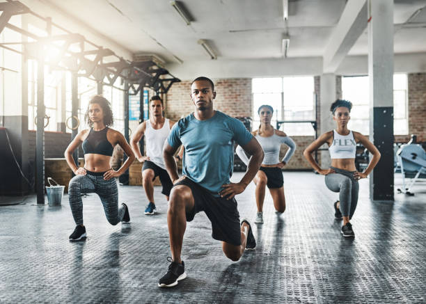 Every step taken towards fitness pays off Shot of a group of young people doing lunges together during their workout in a gym health club stock pictures, royalty-free photos & images