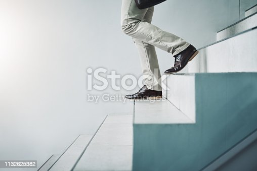 Closeup shot of an unrecognizable businessman walking down a staircase in an office