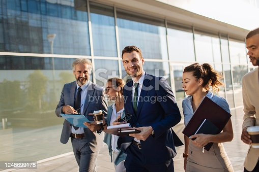 Five coworkers walking next to an office building