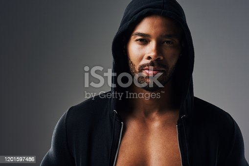 Portrait of a handsome young man wearing a hoodie posing against a grey background