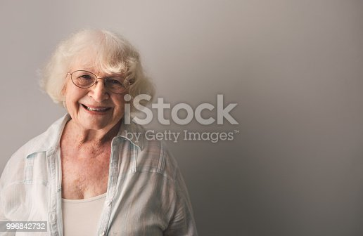 Portrait of a happy senior woman against a gray background