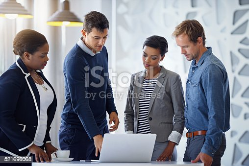Shot of a group of coworkers working together on a laptop in an office