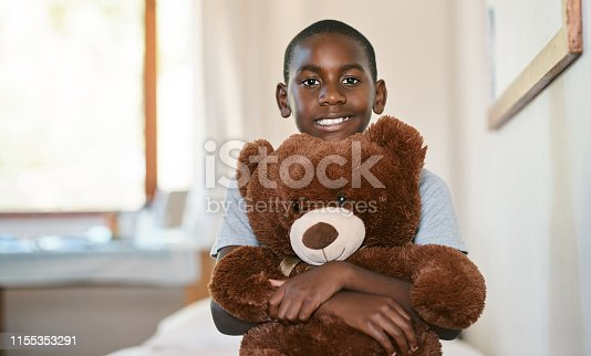 Portrait of an adorable young boy holding a teddybear in a doctor's office