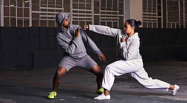 Everybody was kung-fu fighting Shot of a young man and woman practicing martial arts together self defense stock pictures, royalty-free photos & images