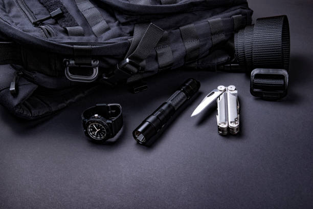 Alltägliche tragen (EDC) Artikel für Männer in schwarzer Farbe - Rucksack, taktische Gürtel, Taschenlampe, Uhr und Silber Multi-Tool. – Foto
