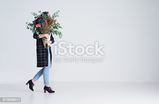 Studio shot of an unrecognizable woman holding flowers against a grey background