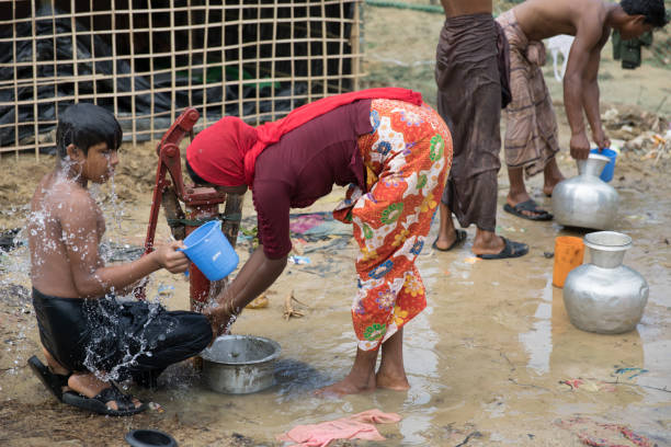 Everyday life in refugee camp for Rohingya in Bangladesh Everyday life in refugee camp for Rohingya in Bangladesh. Refugees taking shower and collecting water from pump. rohingya culture stock pictures, royalty-free photos & images