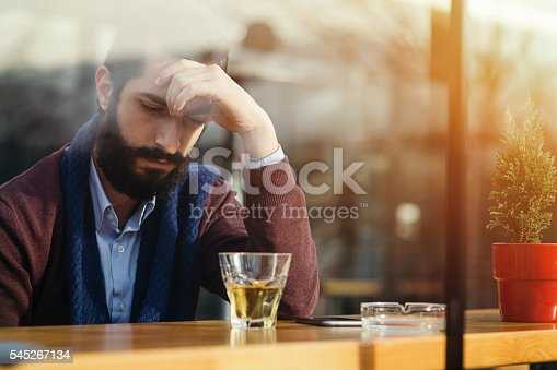 Depressed male drinking alcohol in a bar during daytime