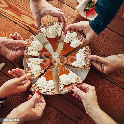 Cropped shot of a group of people each taking a slice of pumpkin pie