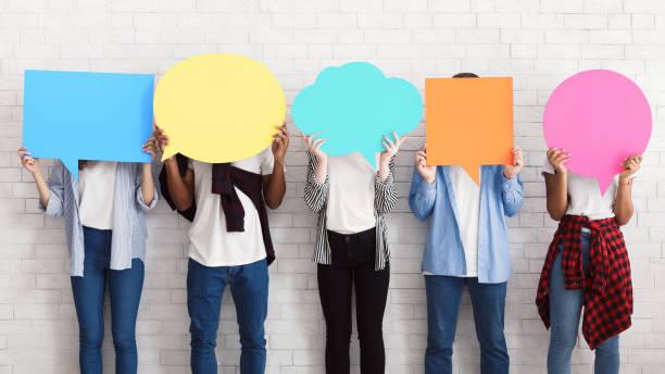 everyone has own opinion. teens holding empty speech bubbles - debate стоковые фото и изображения
