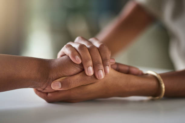 Everyone needs support Cropped shot of two unrecognizable businesswomen holding hands in comfort while sitting in their office mourner stock pictures, royalty-free photos & images