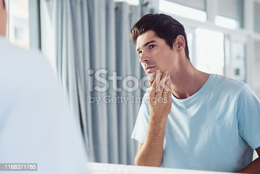 Shot of a handsome young man looking at his face in the mirror at home