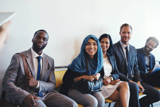 Everyone seems to be excited for the interview Shot of a group of confident businesspeople waiting in line for their interviews inside of a office during the day applicant stock pictures, royalty-free photos & images