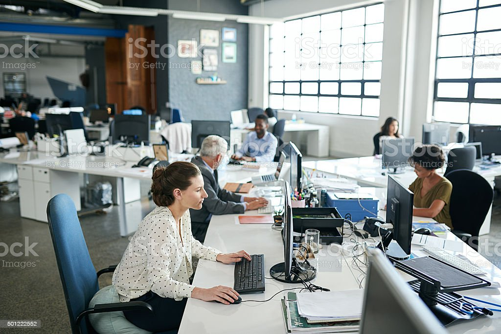 Shot of colleagues working on their computers while sitting in an...