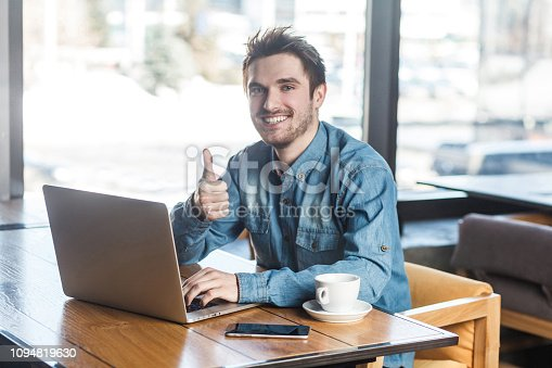 istock Everything alright! Portrait of handsome satisfied bearded young freelancer in blue jeans shirt are sitting in cafe and working on laptop with toothy smile and showing thumb up 1094819630