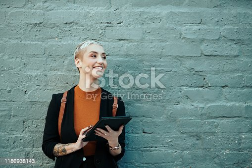 Shot of an attractive young creative businesswoman using a digital tablet while standing against a grey wall outdoors