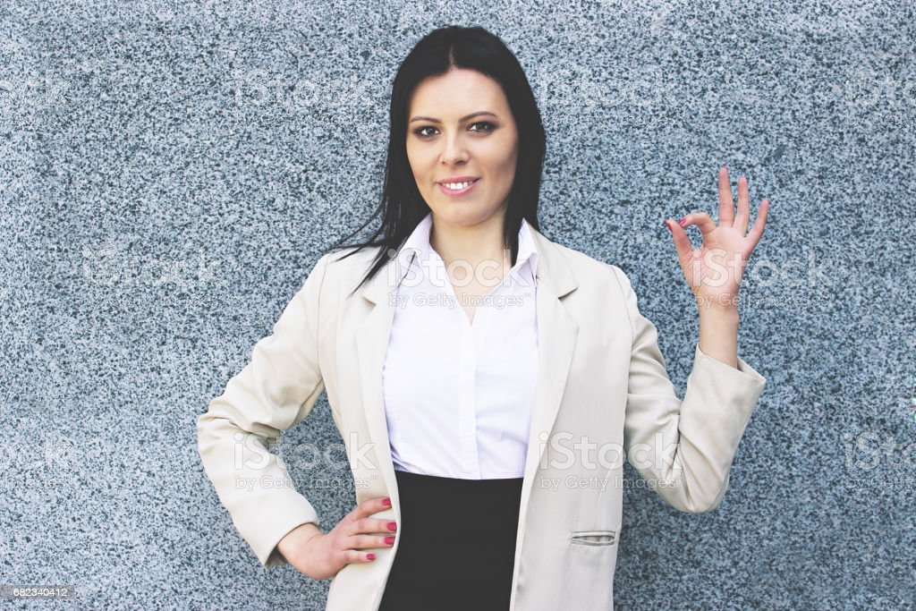 Everything is great. Portrait of cheerful attractive business woman in smart casual wear gesturing and smiling at camera while standing against grey background. zbiór zdjęć royalty-free