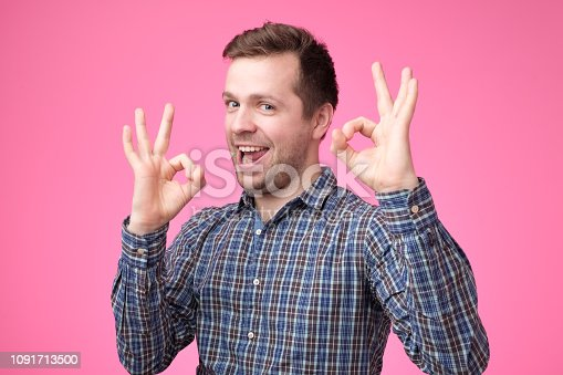 Everything is OK concept. Happy young man gesturing OK sign and smiling while standing against pink background