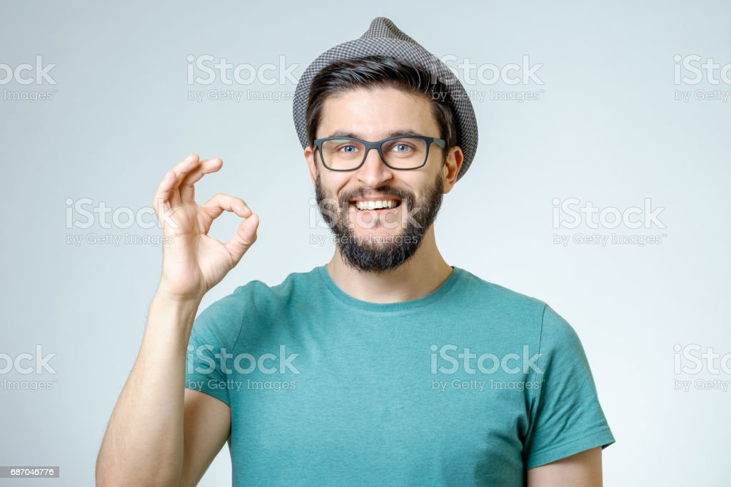 Everything is OK! Happy young man gesturing OK sign and smiling against gray background stock photo