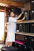 Shot of a focused middle aged man packing boxes away and cleaning his garage at home