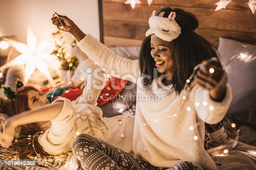 Young woman, wearing payamas and preparing New Year's Eve eve pajama party. She is holding string lights.