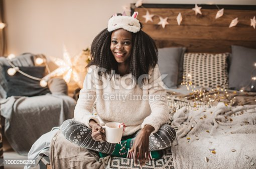 Young woman making New Year's Eve eve pajama party. She is drinking hot chocolate on bed