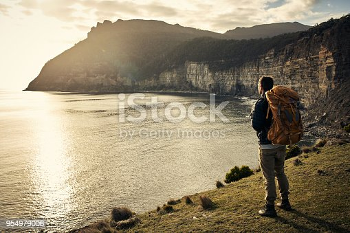 Rearview shot of a handsome young man taking in the sights while hiking in the mountains