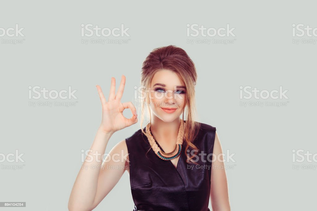 Everything will be alright. Beautiful young happy woman showing Ok sign isolated on light gray wall background. Positive human emotions face expression body language gesture stock photo