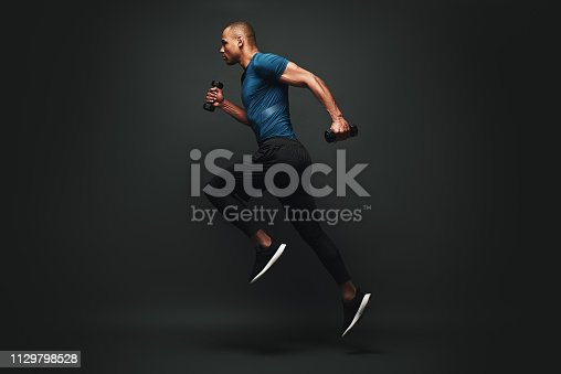 istock Everything you ve ever wanted is on the other side of fear. Dark skinned sportsman jumping over dark background. He is ready to run 1129798528