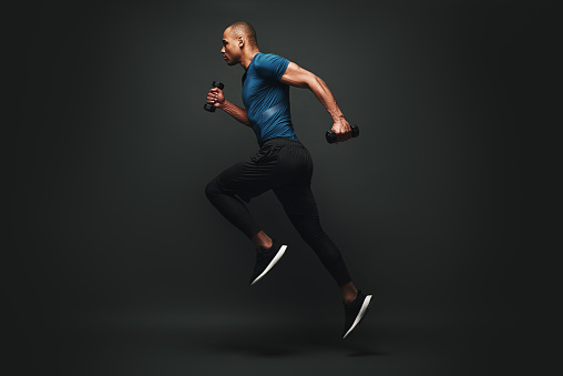 Full length portrait of a healthy muscular sportsman jumping isolated over dark background, with dumbbells in his hands. Dynamic movement. Side view