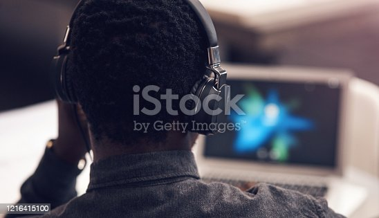 Rearview shot of an unrecognizable businessman using a laptop while wearing headphones in a modern office