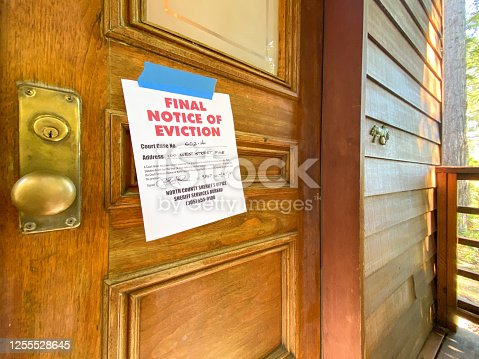 Eviction notice on door of house with brass door knob. Fictitious address, ID, signature and 555 phone number for fictional usage.