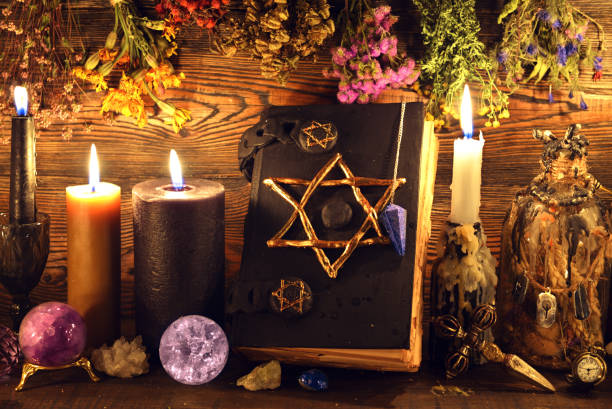 Evil book with pentagram, buning candles, crystal ball, elixir and herbs on witch table. stock photo