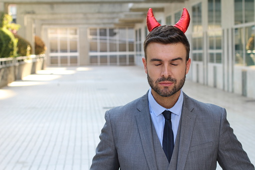 istock Evil businessman with eyes closed and horns 1014312712