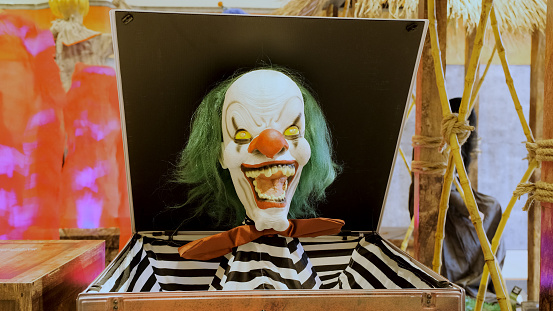 Evil clown coming out of a jack box halloween scene