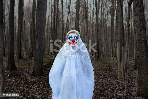 evil clown in a mask standing in a dark forest in a white veil