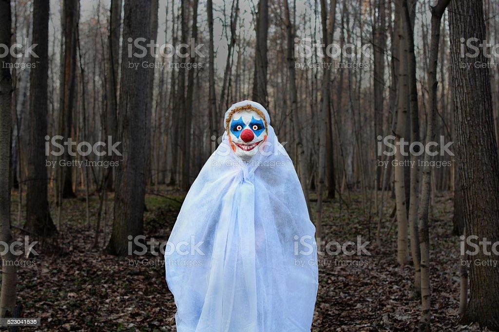 Mal clown dans une forêt sombre dans un voile blanc - Photo