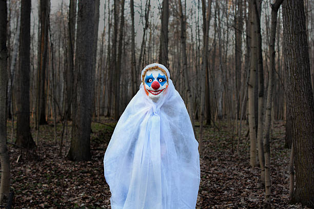 evil clown in a dark forest in a white veil stock photo