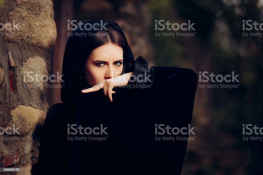 Malvada bruja oscura en capa negra con capucha - foto de stock