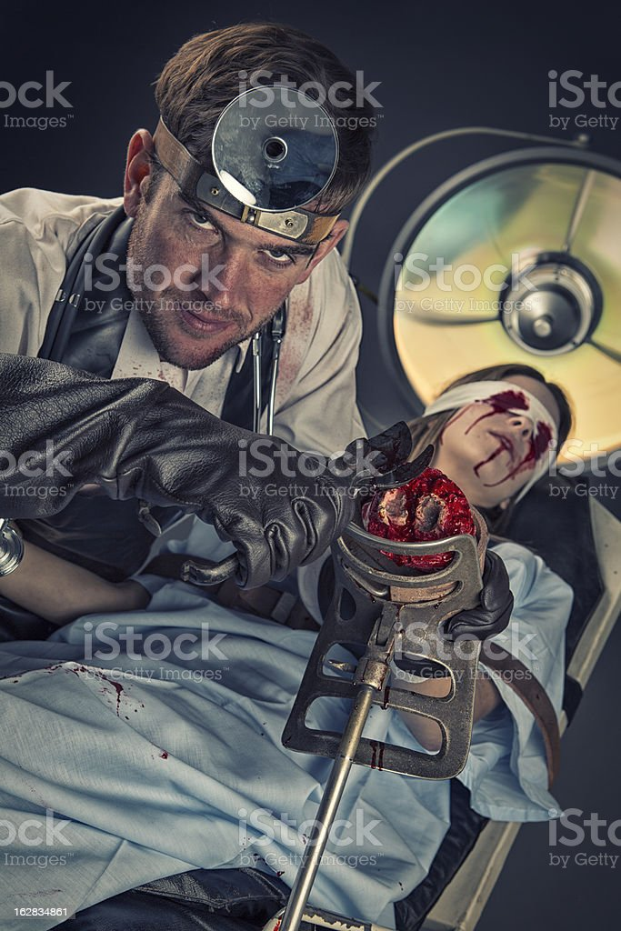 Evil Doctor cutting on missing hand of helpless female victim royalty-free stock photo