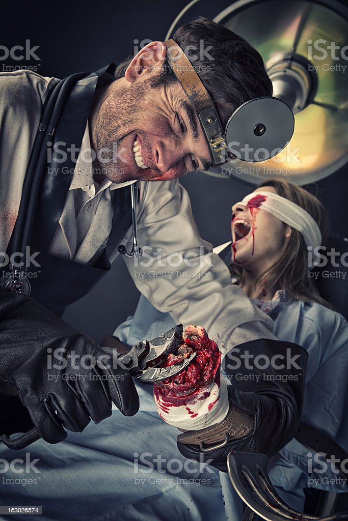 Evil Doctor cutting on missing hand of helpless female victim stock photo