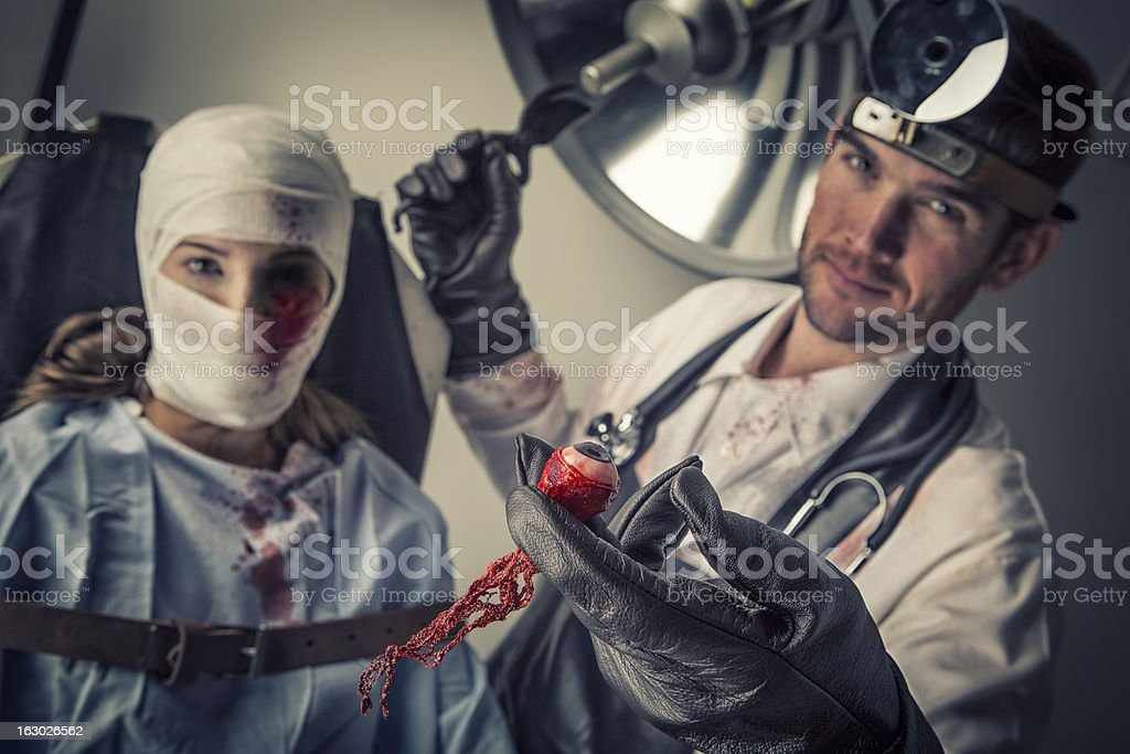 Evil Doctor cutting out the eye of helpless female victim stock photo