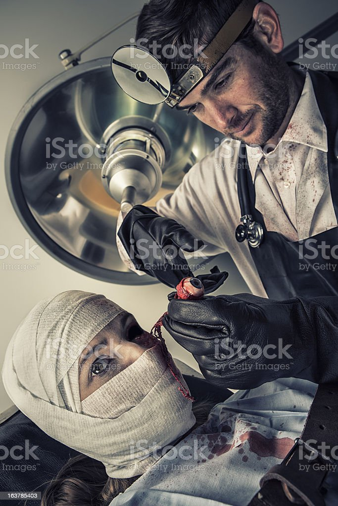 Evil Doctor cutting out the eye of helpless female victim royalty-free stock photo