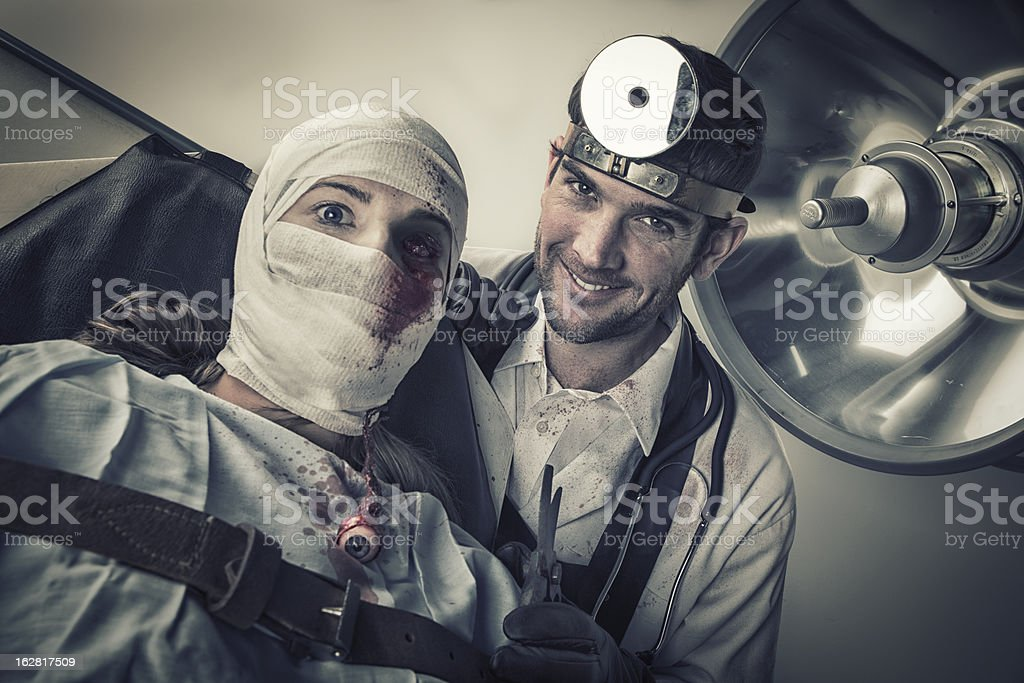 Evil Doctor torturing helpless female victim stock photo