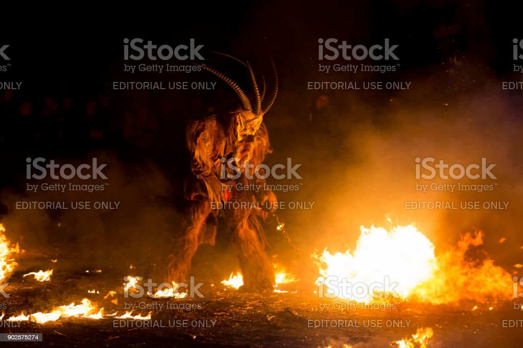 Evil Krampus character stirring the fire stock photo