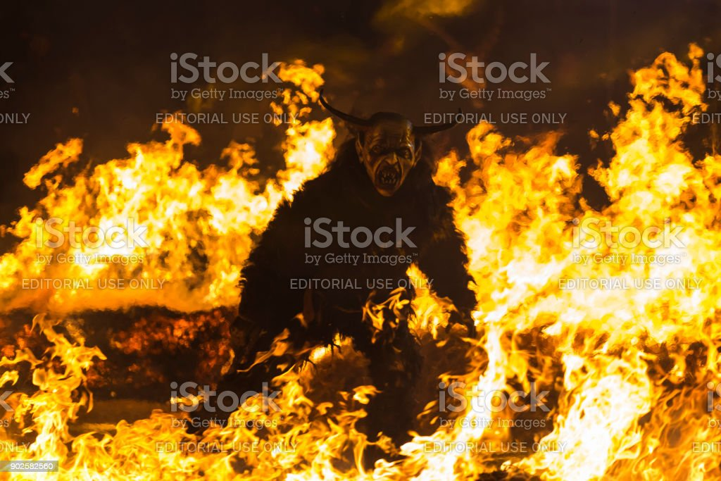 Evil Krampus character walking on fire stock photo
