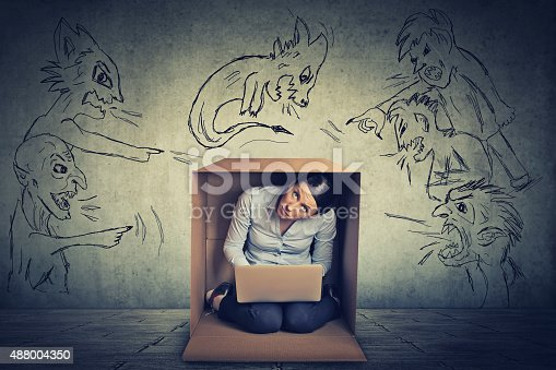 istock Evil men pointing at stressed woman sitting in a box 488004350